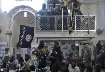 Members of the al Qaeda-linked group, Ansar al-Sharia, hold their weapons as they stand inside a mosque during a news conference during which the group announced the release of army soldiers in the southern town of Jaar