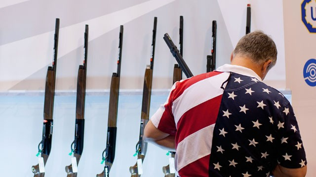 man-in flag-shirt-examines-guns-nra