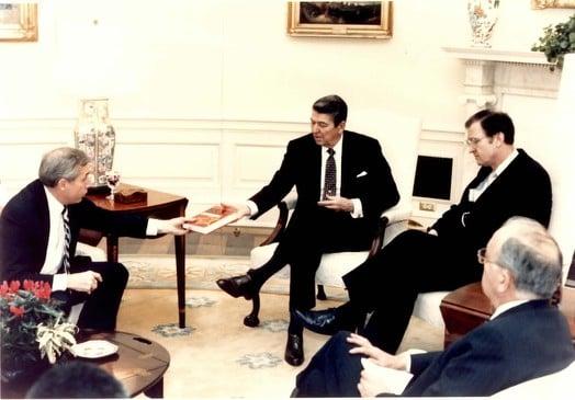 "Rep. Frank Wolf, R-Va., hands President Reagan a manuscript of Pacepa's book ""Red Horizons"""