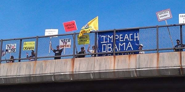 Americans seeking Barack Obama's impeachment display messages from an overpass.
