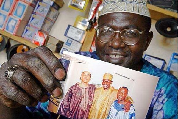 Malik Obama displays a 1980s-era photograph of Barack Obama in Kenya, wearing African garb