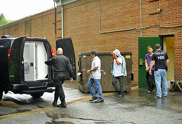 Workers are led out the back door of the Fuji & Jade Garden restaurant and loaded into a state attorney general office's van. Photo: Centre Daily Times