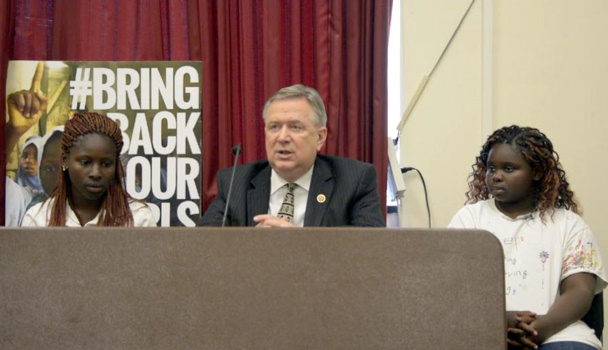 Congressman Stockman and two young girls who are victims and survivors of Boko Haram. Left of Stockman is Debbie Peter. Her brother and father were killed by Boko Haram, and she was tied down, lying in the middle, beside their dead bodies.
