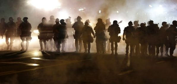 Police in Ferguson, Missouri, during a fourth night of violence after the police shooting of a black teen.
