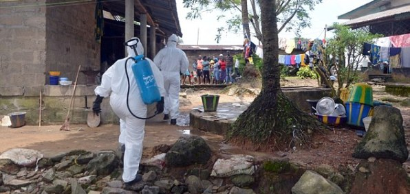 Nurses in protective gear enter a Liberian village.