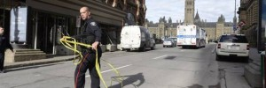 Police cordon off a street as Peace Tower at Parliament Hill can be seen in the background.