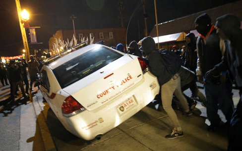 Ferguson protesters attempt to overturn a police car following decision not to indict Officer Wilson