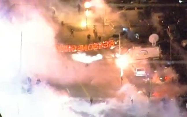Scene outside Ferguson Police Department as tear gas fills the streets after protesters become violent