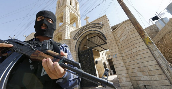 An ISIS terrorist guards the entrance to a church in Iraq.