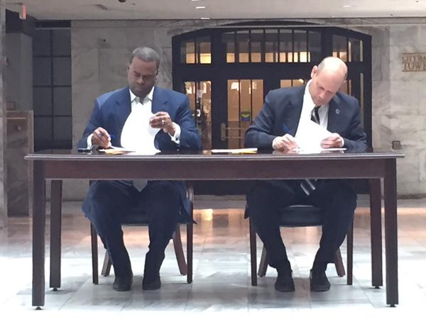 "Kasim Reed signs ""new Americans"" agreement with Leon Rodriquez, head of U.S. Customs and Immigration Service on April 23."