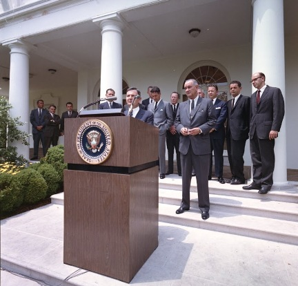 David Rockefeller takes the podium as President Lyndon Johnson looks on in the White House Rose Garden on June 15, 1964, to announce the launch of the International Executive Service Corps.