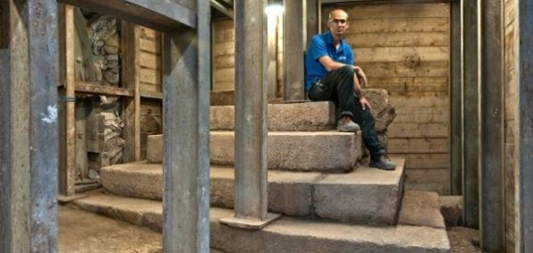 Joe Uziel, co-director of the excavation from the Israel Antiquities Authority, sitting atop the stepped structure from the Second Temple period. (Photo: Shai Halevy, courtesy Israel Antiquities Authority)
