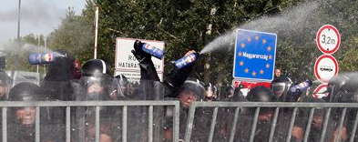 Hungarian police spray rioting Muslims with water cannons and tear gas Wednesday.