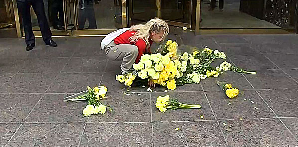 The woman's protest fails miserably when she drops the flowers on the ground.