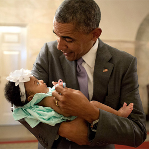 President Obama holds a baby of a former staff member (White House photo)