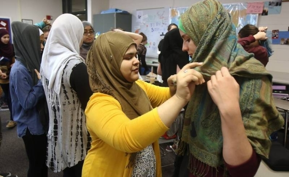 A Muslim student helps a non-Muslim girl to properly wear her hijab for the day at Vernon Hills High School in Chicago last week.