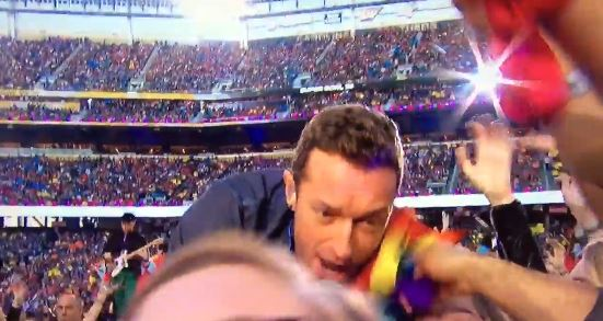 Coldplay's lead singer allows a fan to dust his face with a rainbow flag.