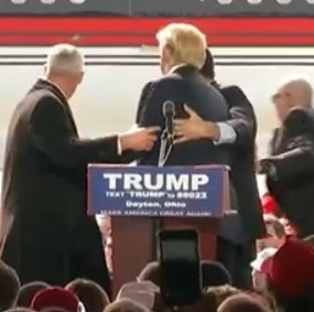 Donald Trump is shielded by Secret Service agents as a protester tries to rush the stage in Cleveland, Ohio