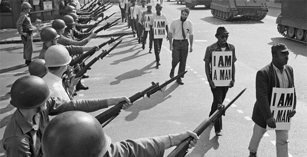 U.S. National Guard troops block off Beale Street as civil rights marchers wearing placards reading, 'I AM A MAN' pass by on March 29, 1968