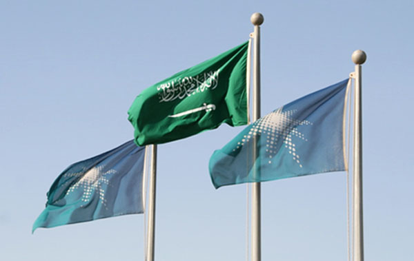 The flags of the Kingdom of Saudi Arabia and Saudi Aramco fly side by side in Dammam, Saudi Arabia (Photo: Anthony C. LoBaido)