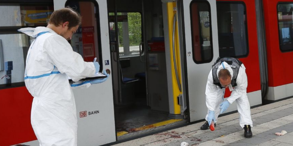 Forensic police examine the site of a knife attack at a train station near Munich, Germany.