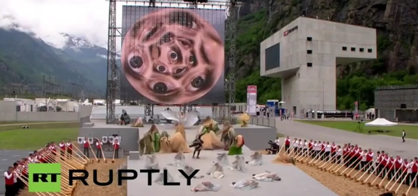 A circle of all-seeing eyes watches as people bow down during opening ceremony for the world's longest and deepest rail tunnel in Switzerland.