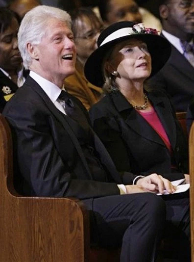 Bill and Hillary Clinton attend a funeral