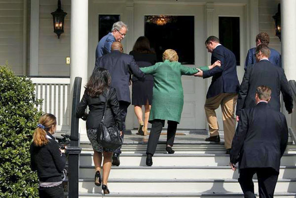 Hillary Clinton being helped up the stairs