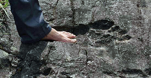 A man stands in a mysterious giant footprint in hardened rock in China (Sina news agency)