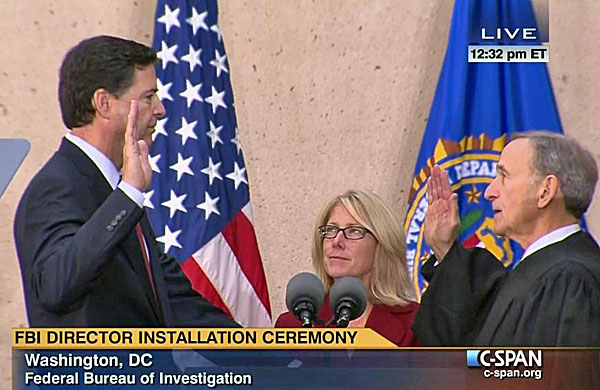 James Come, left, gets sworn in as FBI director as his wife Patrice, center, looks on