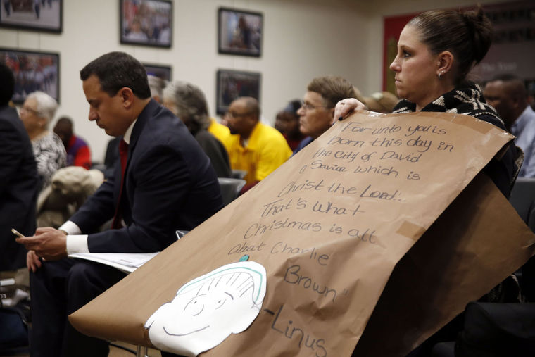 Dedra Shannon holds hold her banned Christmas poster during the Killeen Independent School District board meeting Dec. 13.