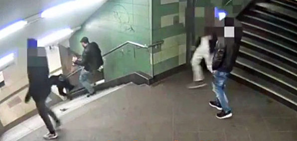 A man kicks a young woman down a floght of stairs in a Berlin, Germany, subway station. (Video screenshot)