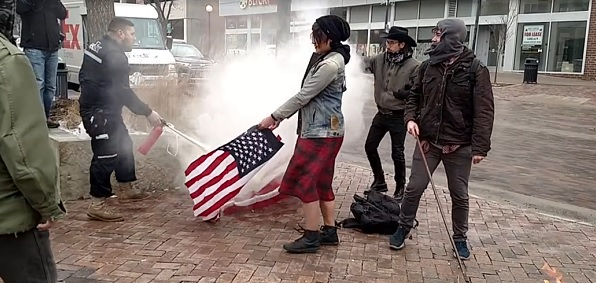 FedEx driver Matt Uhrin extinguishes U.S. flags being burned by protesters (Screen capture)