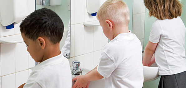 Children standing in line washing their hands in a primary school bathroom