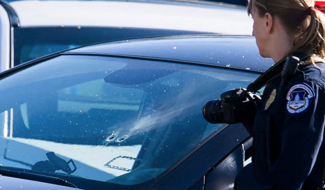 A Capitol police officer examines bullet holes in a car that that was involved in an incident outside the U.S. Capitol in Washington, March 29, 2017.