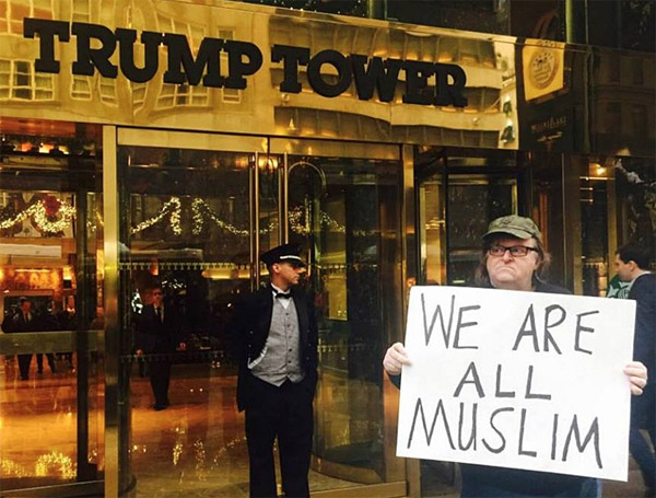 Leftist activist Michael Moore stands in front of Trump Tower in New York City holding a sign declaring, 'We are all Muslim' in December 2015 (Twitter/@MMFlint)