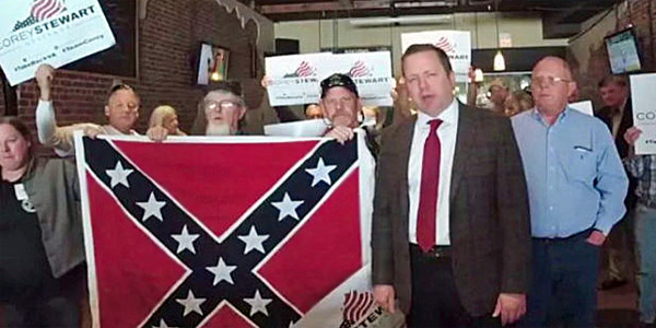 Corey Stewart, who is running for Virginia governor, stands beside the Confederate flag (Photo: PoliticusUSA)