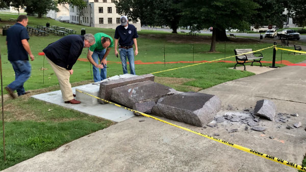 Investigators examine a destroyed Ten Commandments monument on the grounds of the Arkansas state capitol.