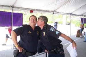 Sgt. Stephen Allen, right, kisses another officer to mock Christians (Florida Family Policy Council)