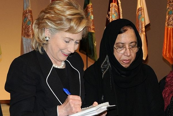 Former Secretary of State Hillary Clinton signing autographs with Saleha Abedin in Saudi Arabia