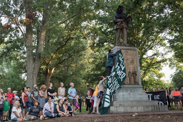 Protesters drape a flag that reads 'Rest in Power: Heather Heyer' over the Silent Sam monument. Heyer was hit and killed by a car that drove into a crowd during the Charlottesville protests (Photo: UNC Daily Tarheel)