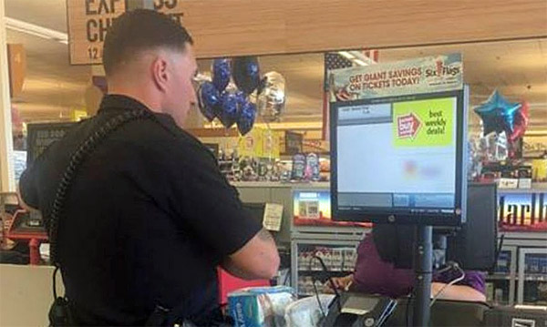 Rookie Officer Bennett Johns purchasing diapers for woman accused of stealing them (Laurel, Maryland, Police Department via Facebook)