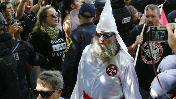 Members of the KKK escorted by police during a July 8, 2017, rally in Charlottesville, Virginia.