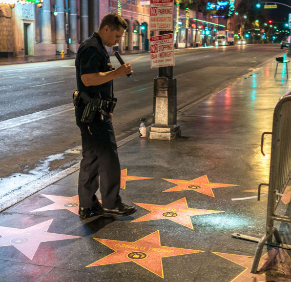 A police officer early Aug. 9, 2018, inspects vinyl stars affixed on the Hollywood Walk of Fame overnight replicating the tribute to Donald Trump that was demolished by a vandal (via Instagram)