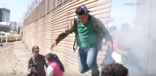 A Central American migrant retreats from a U.S. border fence as an attempt to storm the border is repelled by tear gas (Screenshot KGTV-TV, San Diego)