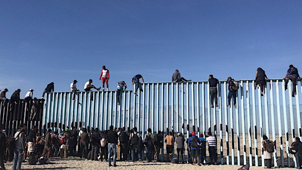Migrants scale a border fence near San Diego on Nov. 13, 2018 (Lizbeth Diaz via Twitter)