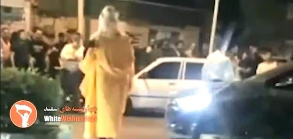 An Iranian woman is confronted by a jeering mob (video screenshot)